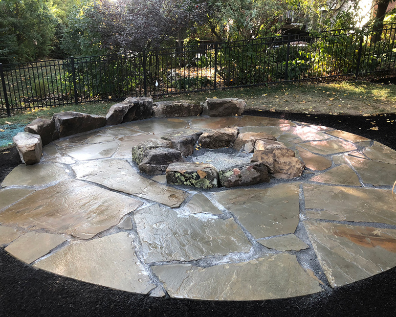 wood burning fire feature with organic stone retaining walls